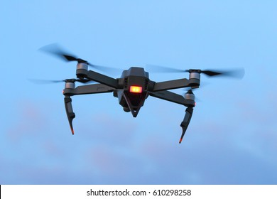 A black spying drone on the evening sky. Crime and terrorism theme.