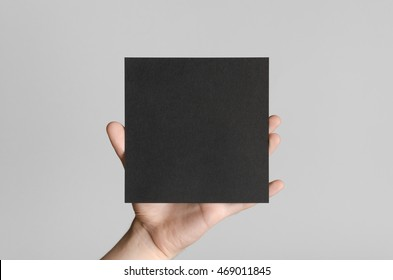 Black Square Flyer / Invitation Mock-Up - Male hands holding a black flyer on a gray background.