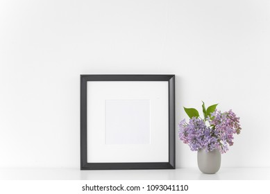 Black square frame with lilac bouquet on white background