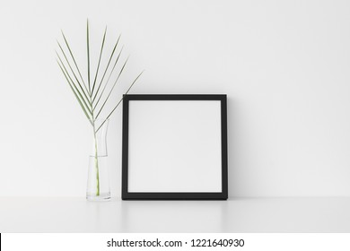 Black square frame mockup with palm leaf in a glass vase.