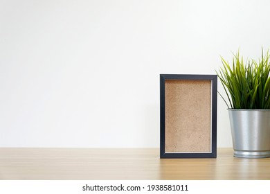 black square frames and green plant on wooden table, empty frames