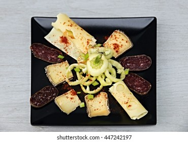 Black square plate with cheese variation, yellow pepper and salami sprinkled with powder red pepper on gray table.