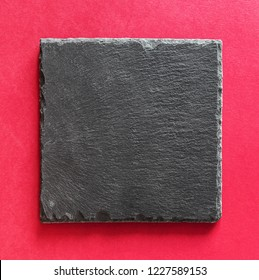 Black square stone plate on red background. Can be used copy space for text. Top view