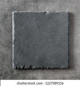 Black square stone plate on dark background. Can be used copy space for text. Top view