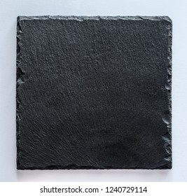 Black square stone plate on gray background. Can be used copy space for text. Top view