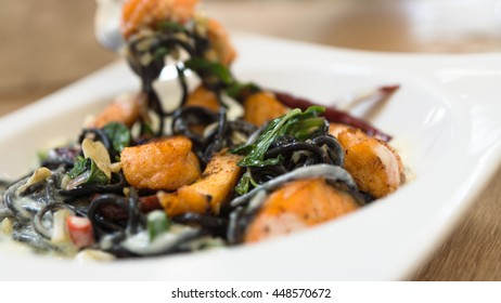 Black squid ink pasta with fried salmon and white cream sauce in white square plate on wooden desk