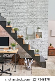 Black stair in the room and wooden desk desktop under the stair. Brick wall frame and lamp concept.