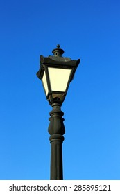Black standard lamp on blue sky background