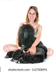 black standard poodle and woman in front of white background