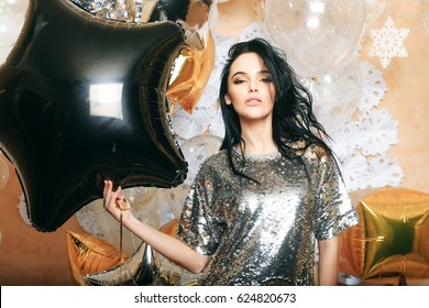 black star balloon, pretty woman or cute sexy girl in silver sequins dress has brunette hair and trendy makeup on face holding festive golden balloons, white snowflakes. party and holiday celebration
