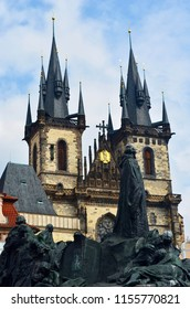 A black statue of Jan Hus stands outside the Church of Our Lady of Tyn, Prague. The church is of brown stone with black turrets. The sky is blue with white clouds.
