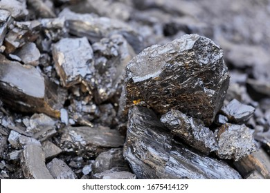 Black steam coal on a rock background. Coal mining. Black gold, a brilliant mineral used by man as a fuel to generate energy and generate heat to heat a house in the cold season.