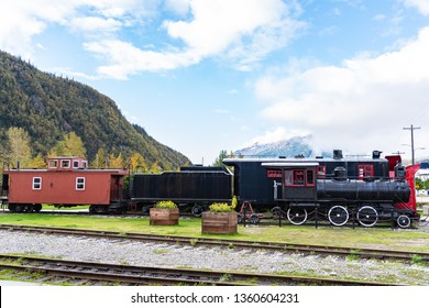 Black Steam Engine/Locomotive 52 and red and black Snow Plow 1 with caboose in public space off Main Street in Skagway, Alaska