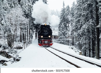 Black steam railway in the winter through the forest