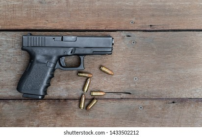 Black steel polymer semi-automatic 9mm pistol on wooden background with Copy Space