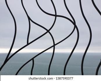 Black steel railing, sea background close up
