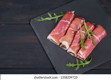 Black stone platter with slices of cured ham or Spanish jamon serrano or Italian prosciutto crudo with arugula. Delicious Italian appetizers