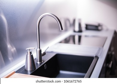 Black stone sink and water faucet in new modern kitchen interior.