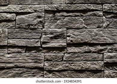 Black stone slate texture background, slate stone wall. decorative tiles for wall decoration. Black brick. loft decor style. structural surface imitating old brick. close-up of black stone wall - Shutterstock ID 1924834391