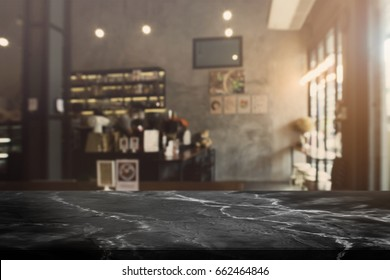 Black stone table top and blurred bokeh cafe and coffee shop interior background with vintage filter - can used for display or montage your products.
