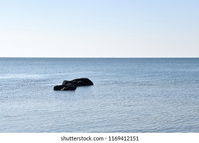 Black stones in calm blue water