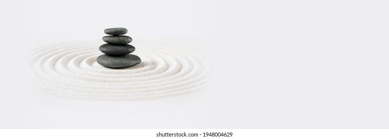 Black stones pile in the sand. Zen japanese garden background scene. Horizontal banner