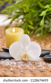 Black stones, white orchid and candle,many salt, green leaves on woven mat