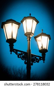 Black street lamp against a blue evening sky (superimposed color filter and added vignette)