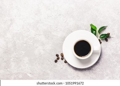 Black strong coffee in white cup, coffee beans and leaves on concrete background. Top view, space for text.