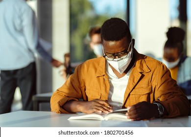 Black student wearing protective face mask while studying in lecture hall during coronavirus epidemic.