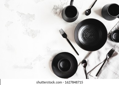 Black stylish tableware on white background. Flat lay, top view