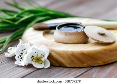 black substance in wooden jar on a wooden background. Black Mask
