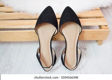 Black suede shoes on a wooden box. Fashionable concept
