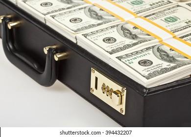 black suitcase full of hundred dollar isolated on white