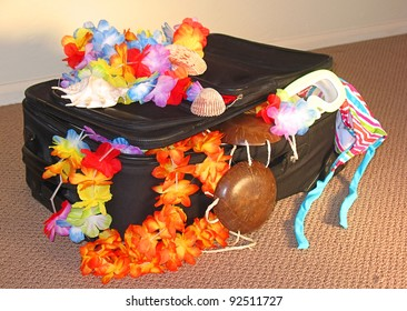Black suitcase sitting on the floor of a hotel.  Leis, coconut bra, and swimming suit hanging out.