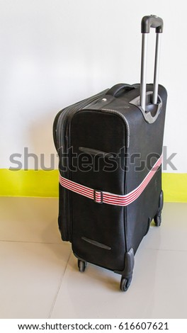black suitcase with white red rope on ceramic floor in room