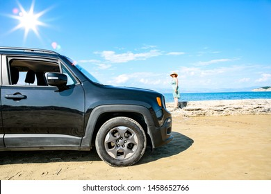 Black summer car on beach and sunny day. Sea landscape and blue sky.