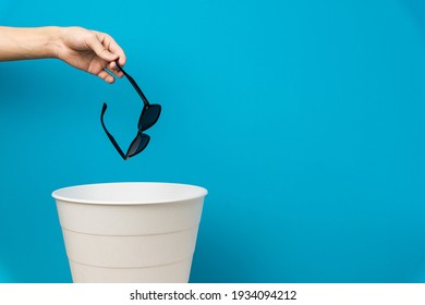 The black sunglasess is thrown into the trash for disposal and recycling