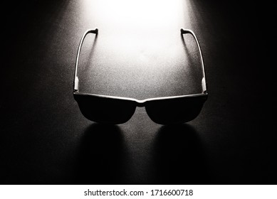 black sunglasses lying on a black table and cast a dark shadow. black minimalism concept