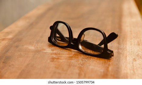 A black sunglasses on a brown wooden surface unique photo