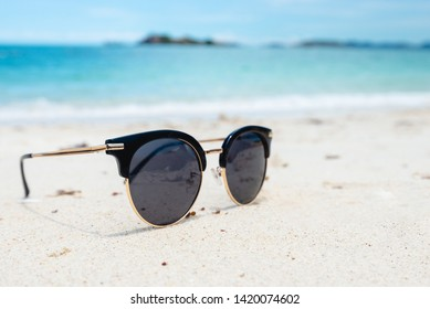 Black Sunglasses on the Sea background. beautiful sand beach as summertime, Travel and vacation concept. Holiday concept. Copy space for message.