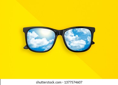 Black Sunglasses with reflection cloud on sky, on yellow background. Creative fashion minimal concept. Summer background. Flat lay. Top view.