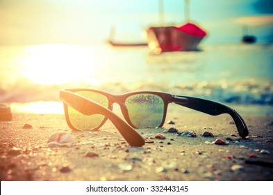 black sunglasses and sea background with blured boat