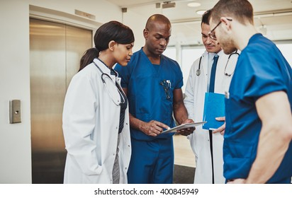 Black surgeon giving instruction to medical team mixed races using tablet