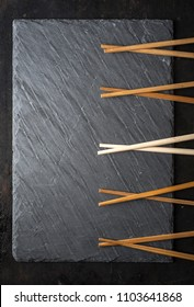 Black sushi slate board with wooden chopsticks with copyspace. Top view. Asian food design background from above.