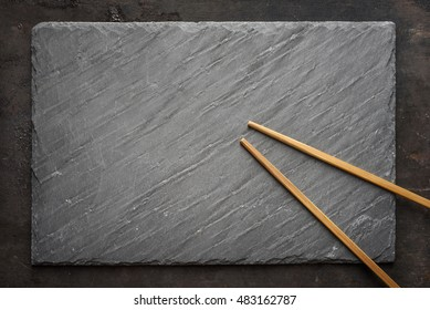 Black sushi slate board with wooden chopsticks with copyspace. Top view.