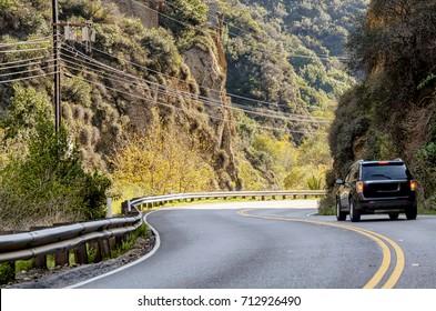 Black SUV driving along winding California highway