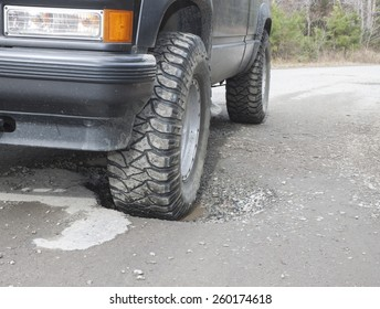 A black SUV with a front wheel sunk in a water filled pothole on an old rural asphalt/dirt road