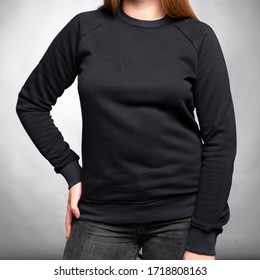 Black sweatshirt jacket with sleeves dressed on a girl on a gray background. Vertical orientation.