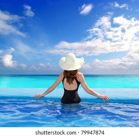 black swimsuit woman rear view in a pool with direct view to tropical Caribbean sea [Photo Illustration]